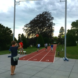 A mother captures her sons' running competition beneath a pole vault apparatus in the Museum gardens.
