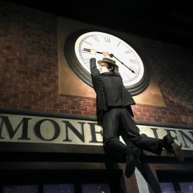 Comedian Harold Lloyd hangs from a clock in a set depicting Chaplin's film The Pawnshop.